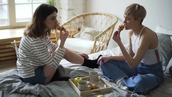 Thumbnail for Young Lesbian Couple Is Eating Croissants Sitting in Bed in Morning at Apartment. Spbd