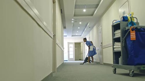 Chambermaid Vacuuming Hotel Hall