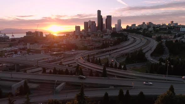 Thumbnail for Drone Shot Of Seattle With Epic Glowing Sunset On Freeway And Downtown Skyscraper Buildings