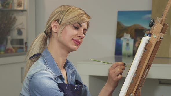 Thumbnail for Beautiful Female Artist Smiling Painting Artwork at Her Studio