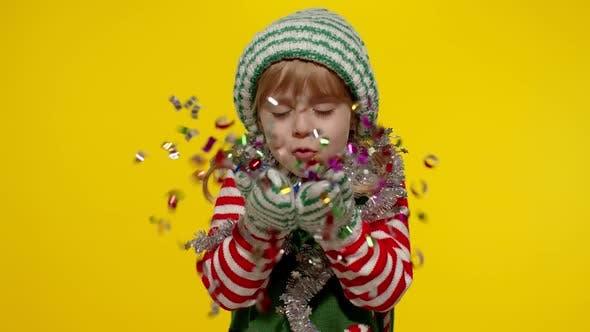 Kid Child Teenager Girl in Christmas Elf Santa Helper Costume Having Fun Blowing Confetti To Camera