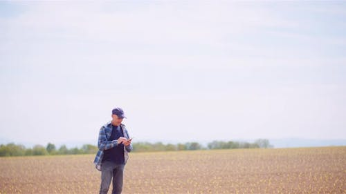 Farmer Using Digital Tablet To Calculate Income From Agriculture Activity