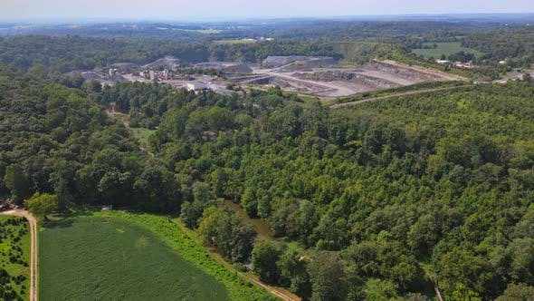 Aerial View of Opencast Mining Quarry with Lots of Machinery at Work in Middle of Forest on