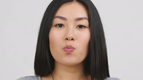 Asian Young Woman Chewing And Blowing BubbleGum White Background