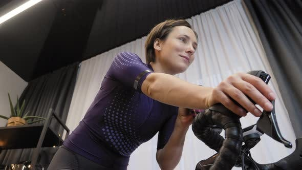 Smiling female is pedaling on smart cycling trainer, drinking water, training at home.