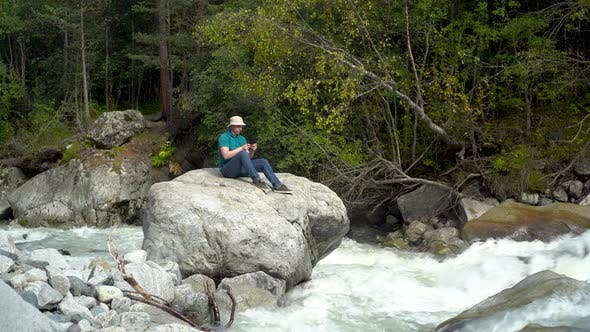 Thumbnail for A Young Man in a Panama Hat Sits on a Stone with a Tablet in His Hands in the Mountains By the River