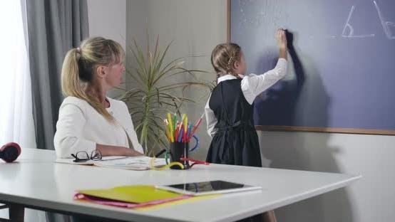Thumbnail for Portrait of Adult Caucasian Teacher Dictating Formula To Little Girl Writing on Blackboard