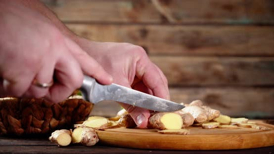 Men's Hands Cut Ginger Into Pieces on a Wooden Cutting Board.