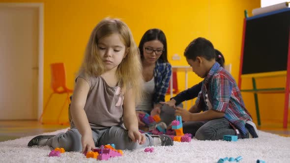 Thumbnail for Preschool Girl Playing with Colorful Toy Blocks