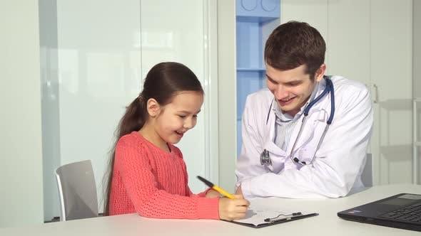 Little girl zeichnet auf clipboard in der Nähe der Arzt