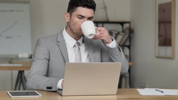 Thumbnail for Businessman Drinking Coffee and Working on Laptop