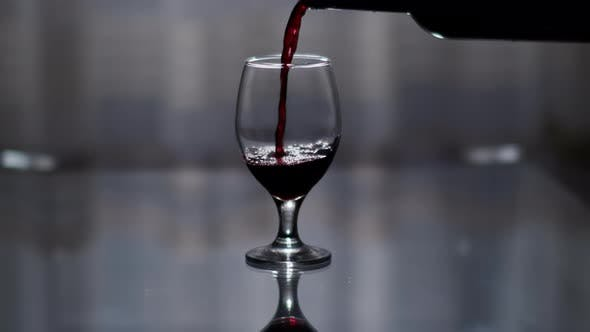 Silhouette of a glass with red wine pouring from a bottle, on a dark background