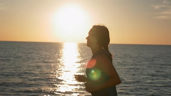 Thumbnail for Sportive fitness woman is running along sea coastline in the morning at sunrise.