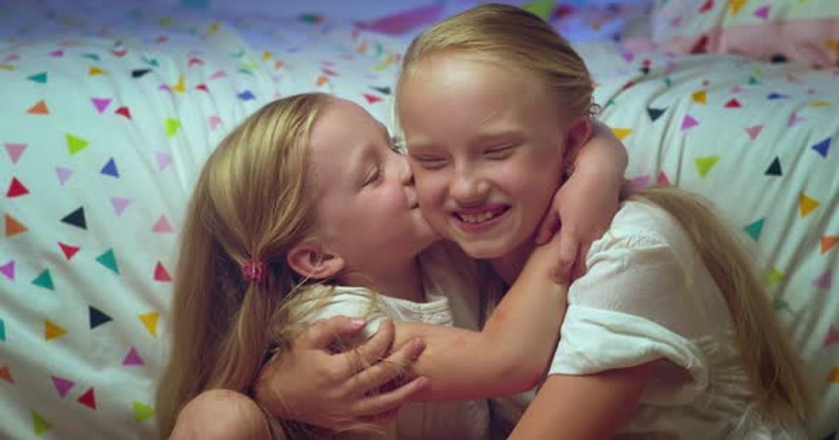 Two Smiling Sisters Girls Hug Tightly Each Other