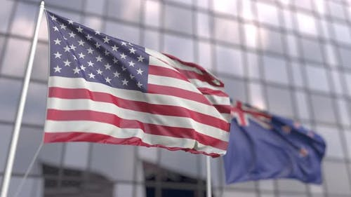 Waving Flags of the USA and New Zealand in Front of a Skyscraper
