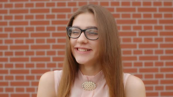 Cover Image for Portrait of a Girl Student Wearing Glasses That Laughs and Smile Against a Brick Red Wall