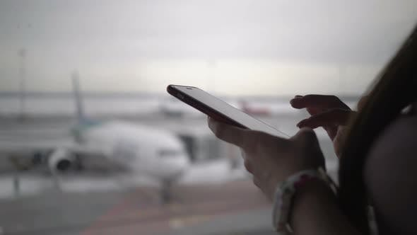 Thumbnail for Woman Using Mobile Phone at Airport Terminal and Waiting for Boarding the Plane