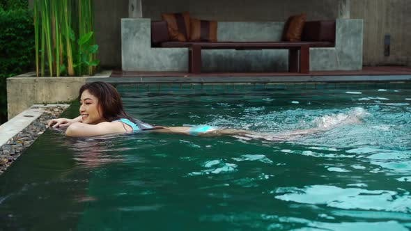 slow-motion of woman hold on to the edge of the swimming pool and splashing water with her feet