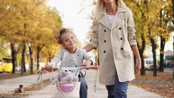 Thumbnail for Little Girl Learns To Ride Bike with Support of Mom