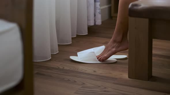 Waking Up in Hotel Room Woman is Putting White Slippers for Guests Closeup View
