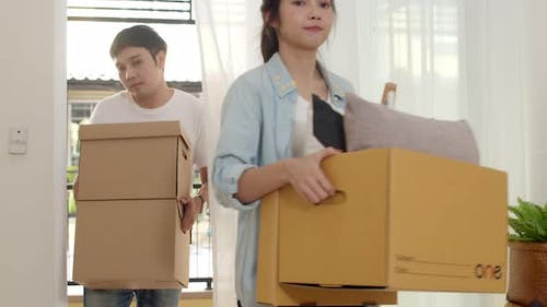 Korean family unpacking or packing boxes and hold cardboard boxes for move object walking into home.