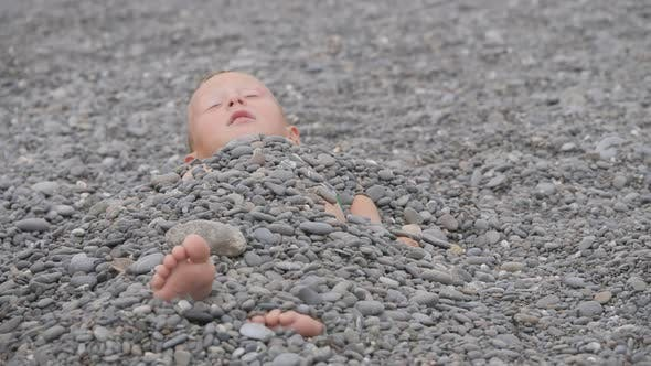 Thumbnail for Child Lies Covered with Pebbles.