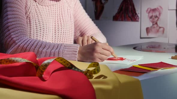 Thumbnail for Designer's Hands Draw a Sketch of a Beautiful Red Dress. Close Up