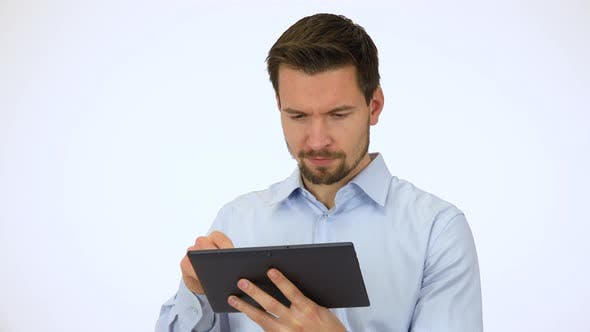 Thumbnail for A Young Handsome Man Works on a Tablet, Then Smiles at the Camera - White Screen Studio