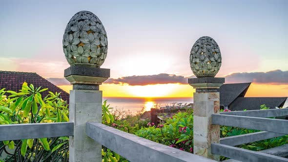 Cover Image for The Sculpture Sand Stone of Lantern Floral Pattern on Sunrise and Sea Background in Amed Beach, Bali