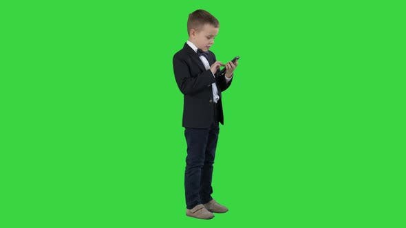 Young Boy in Elegance Suit Playing with Mobile Phone on a Green Screen, Chroma Key.