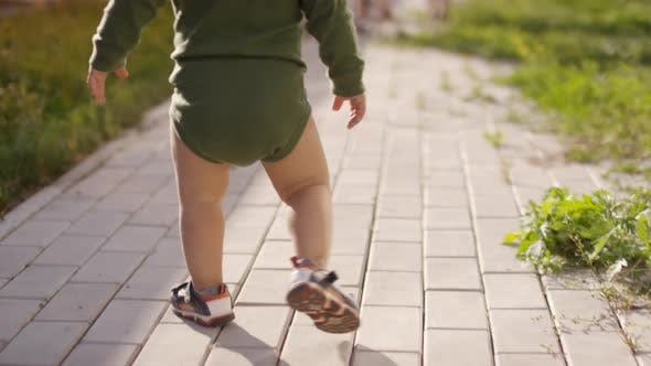 Thumbnail for Legs of Unrecognizable Toddler Walking on Footpath in Garden
