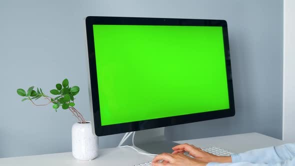 Thumbnail for Woman Typing on a Computer Keyboard, Monitor with a Green Screen. Chroma Key. Copy Space.