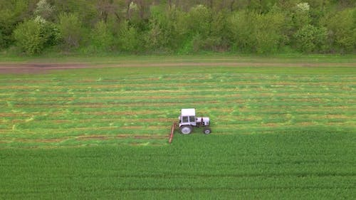 Mowing with a Agriculture Machine Tractor with Mowers on the Big Farm Field