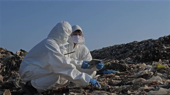 Scientist wearing personal protective equipment (PPE) at landfill site
