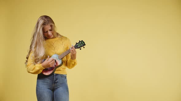 Thumbnail for Blonde Woman Playing a Ukulele with a Yellow Background