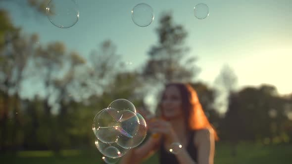 Thumbnail for Portrait of Beautiful Ginger Young Woman. Blowing Bubbles in the Park