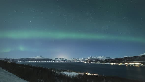 Green Northern Lights and Snowy Mountains at Winter Night. Troms, Norway