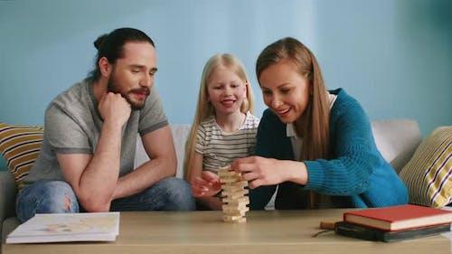 Young Family Has Fun Playing Jenga