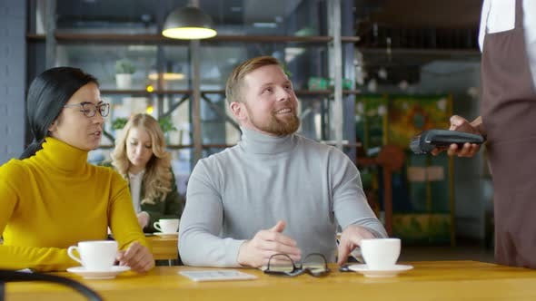 Cover Image for Man Paying with Smartphone on Coffee Break with Colleague in Cafe