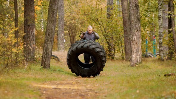 Thumbnail for A Big Man Bodybuilder Turning Over the Tire on the Ground and Moving It Forward - Training Outdoors