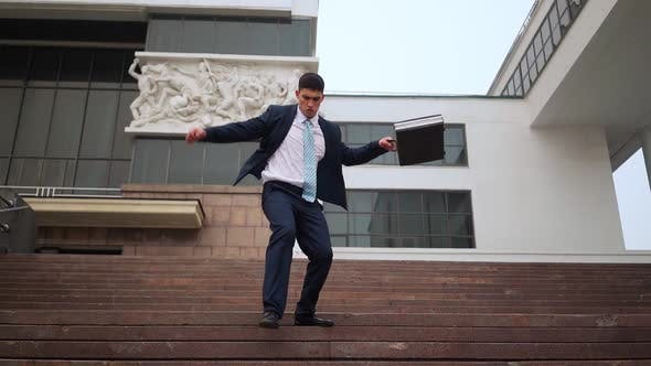Thumbnail for Happy Successful Businessman Playfully Descends Stairs Near Office Building