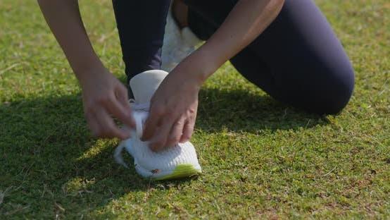 Woman fix shoelace at park