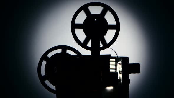 Thumbnail for Silhouette Dark Studio. Vintage Movie Projector Turns the Tape