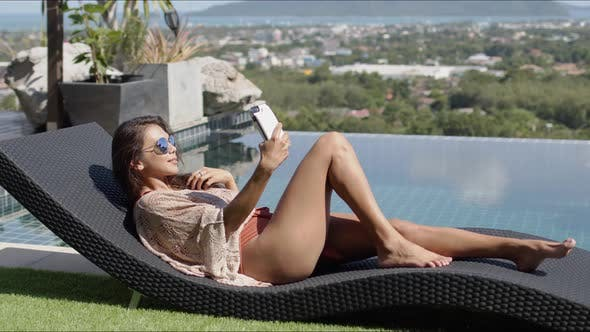 Thumbnail for Lounging Female Taking Selfie at Poolside on Top of Hotel