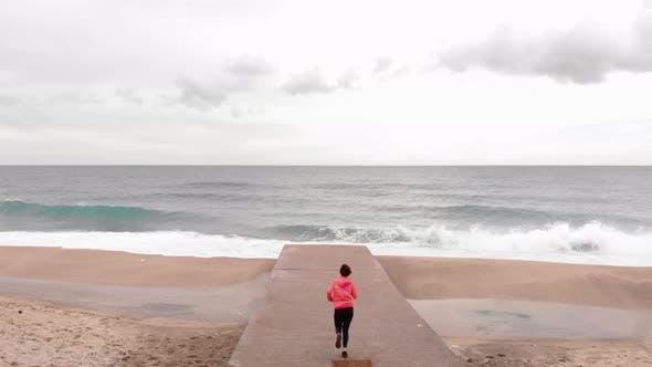 Sportliche Frau läuft zum Rand des Seepiers und bewundert atemberaubende schöne Landschaft