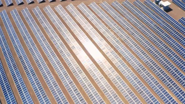 Thumbnail for The Reflection of Afternoon Sun Moves Over the Rows of Blue Solar Panels. Aerial Topdown View.