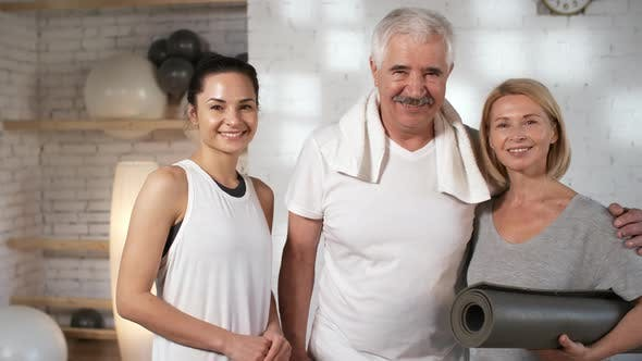 Cover Image for Delighted Customer Couple Posing with their Yoga Teacher at Studio