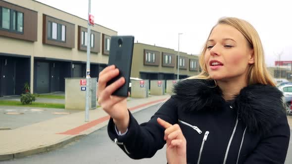 Young Blonde Woman Takes Selfie Photos on Street, Buildings in the Background