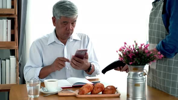 Thumbnail for Elderly Asian Man Using a Mobile Phone Smart Payment
