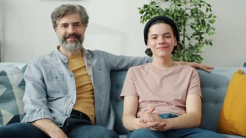Portrait of Happy Family Father and Teenage Son Sitting at Home Smiling Looking at Camera